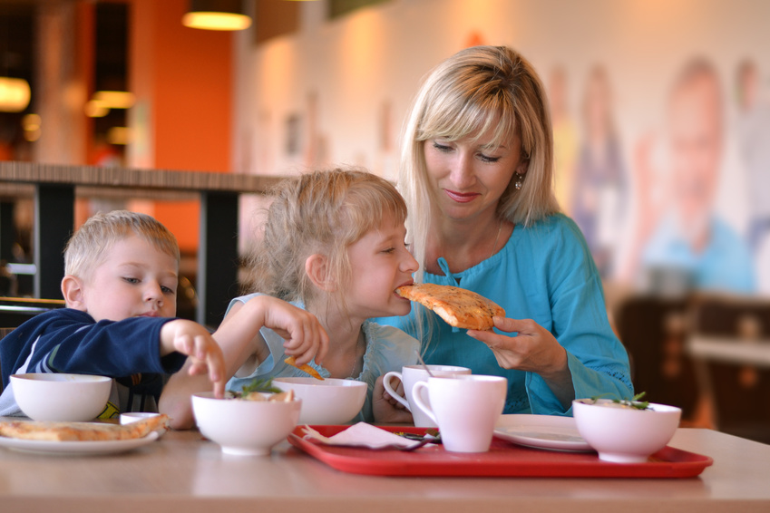 The young woman and two children eat in cafe